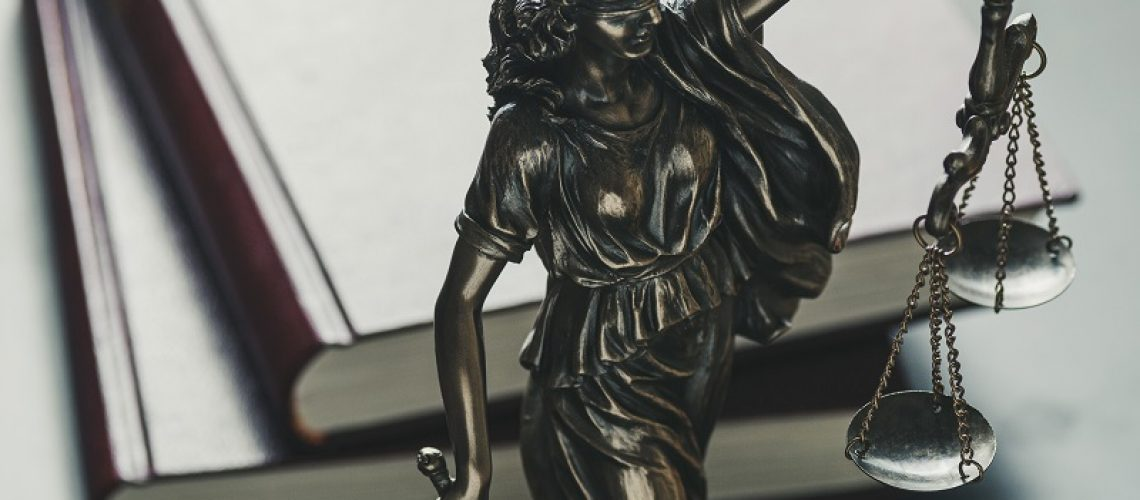 Statue of the figure of Justice holding scales and a sword high angle against law books in court symbolic of the law